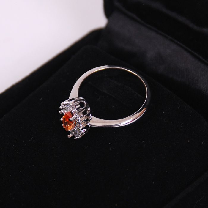 Sparkling silver ring studded with orange sto