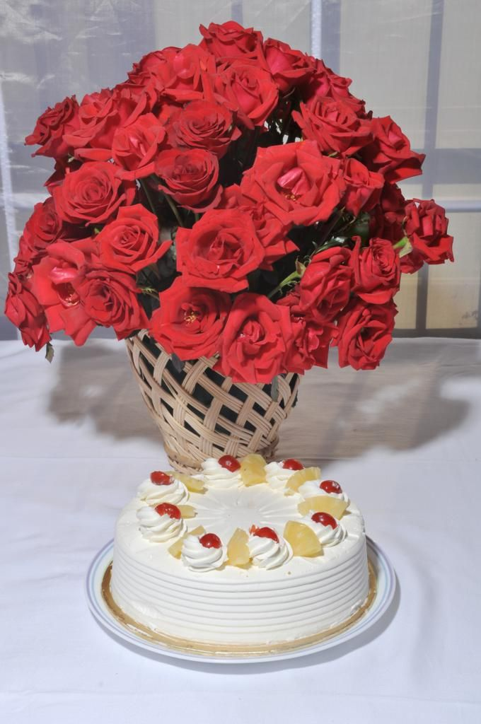 Red Roses in a Cane Vase with Cake